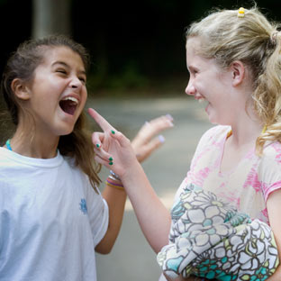 Two girls share a joke at camp.